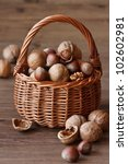 Delicious nuts in a wicker basket on a wooden board. - stock photo