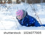 Small photo of Little baby girl crawls all fours on snow in sunny winter park