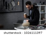 man with coffee in hand sitting ... | Shutterstock . vector #1026111397