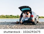 cheerful couple sitting in car... | Shutterstock . vector #1026292675