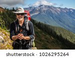 Hiker poses in front of mountain peaks range hiking backpacker old older aarp strong strength vital energetic landscape photography portrait background colorful adventure retired retirement outdoor