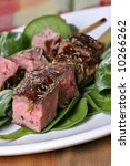 Juicy Beef Steak Skewers Over Spinach - stock photo
