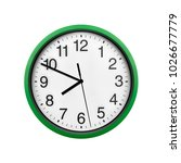 Small photo of Green wall clock isolated on white background. Seven forty-nine on the clock.