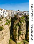 Small photo of Ronda, Spain: Landscape of white houses on the green edges of steep cliffs with mountains in the background. on the green edges of steep cliffs with mountains in the background.
