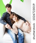Small photo of relationships, love, parentage concept. on the comfortable white couch there are young and wonderful woman that are expecting a baby soon, she is half lying on the knees of her attractive husband