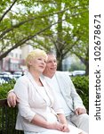 mature couple sitting on bench... | Shutterstock . vector #102678671