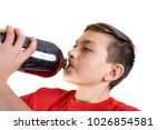 Young caucasian teenage boy drinking a cola drink from the bottle - stock photo