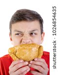 Young caucasian teenage boy eating a cornish pasty - stock photo