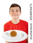 Young caucasian teenage boy holding a scotch egg on a plate - stock photo