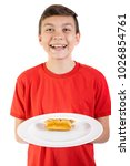 Young caucasian teenage boy with a sausage roll on a plate - stock photo