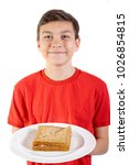Young caucasian teenage boy with a sandwich on a plate - stock photo