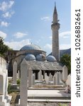 Small photo of MOSTAR, BOSNIA AND HERZEGOVINA - AUGUST 17 2017: Architectural view of Nesuh Aga Vucjakovic Mosque, rurrounded by graves of people killed during the war