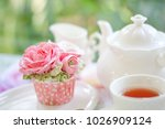 Stock photo a sweet pink rose cup cake with tea pot and cup on the table in the english garden 1026909124