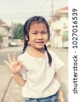 Small photo of asian children hand sign all right with smiling face outdoor