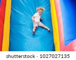 child jumping on colorful... | Shutterstock . vector #1027027135