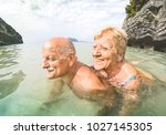 Small photo of Senior couple vacationer having genuine playful fun on tropical beach in Thailand - Snorkel tour in exotic scenario - Active elderly and travel concept around the world - Warm afternoon bright filter