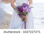 the bride is holding in hands... | Shutterstock . vector #1027227271