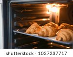 Baking tray with delicious croissants in oven - stock photo