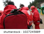 Small photo of Paramedics from mountain rescue service provide first aid during a training for saving a person in accident. Portable Radio on the backpack. Unrecognizable people.