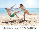 girl pushing a boy at the beach. | Shutterstock . vector #1027261855