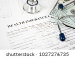 health care costs. stethoscope... | Shutterstock . vector #1027276735