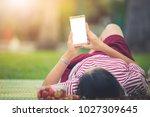 women who are using smartphones ... | Shutterstock . vector #1027309645