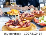 people eating pulpo a la... | Shutterstock . vector #1027312414