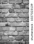 Small photo of Old deteriorated brick wall texture background in black and white with vignetting.