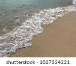 sea wave with bubbles hits the... | Shutterstock . vector #1027334221