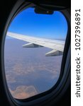 Small photo of View from aircraft window with aircraft wing on blue sky background