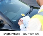 police officer giving a ticket... | Shutterstock . vector #1027404421