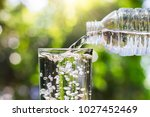 Small photo of Drinking water pouring from bottle into glass on blurred fresh green nature bokeh background, healthy drink concept