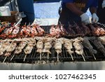 bbq squid on a stick. squid... | Shutterstock . vector #1027462345