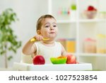 funny baby one year old eating... | Shutterstock . vector #1027523854