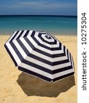 Striped umbrella against sandy beach and ocean - stock photo