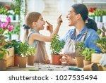 cute child girl helping her... | Shutterstock . vector #1027535494