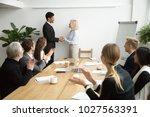 senior female boss promoting... | Shutterstock . vector #1027563391