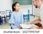 serious schoolgirl listening to ... | Shutterstock . vector #1027590769