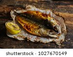 fish with lime on parchment... | Shutterstock . vector #1027670149