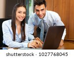 smiling business people using a ... | Shutterstock . vector #1027768045