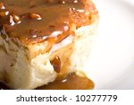 fresh hot bread pudding topped with caramel syrup and pecans - stock photo