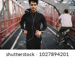 Small photo of Portrait of motivated fit man with sport goal listening music during run on bridge to maintain vital tone.Sportsman dressed in tracksuit training in urban settings while enjoying songs in earphones
