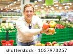 young single man showing fruit...   Shutterstock . vector #1027973257