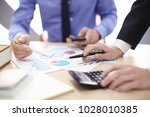 men working at table in office  ... | Shutterstock . vector #1028010385
