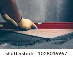 working tiles lay a large tile... | Shutterstock . vector #1028016967