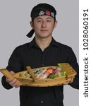 Small photo of Asian cook holding a sushi Japanese food set on wood board, wearing black bandana with Chinese word translation ( Victory )