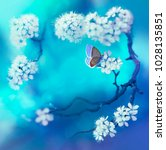 Stock photo spring floral background with flowering cherry branch and butterfly on a blue background in nature 1028135851