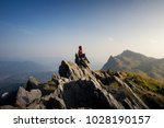 women tourists sit at the top... | Shutterstock . vector #1028190157