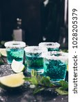 Small photo of Alcohol shots on metal tray. Shooter glasses of blue vodka or Tequila on black table. Mojito with mint