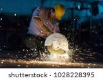 Small photo of Low light image of Worker ware yellow helmet kneel use electric steel cutter machine. He has a Hard work in Factory or garage. Industry in construction site concept.